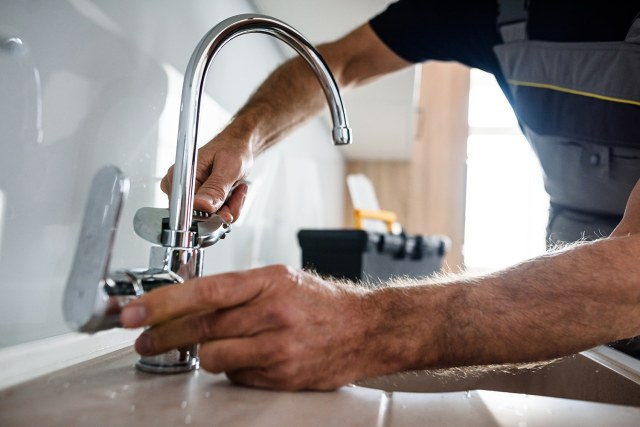 Close up of hands of aged repairman in uniform working, fixing broken kitchen tap using adjustable wrench. Repair service concept. Selective focus. Horizontal shot